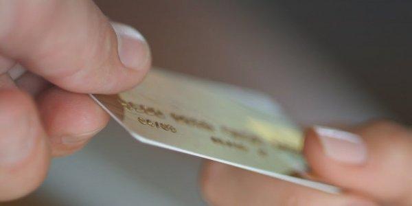 pessoa segurando um cartão de crédito